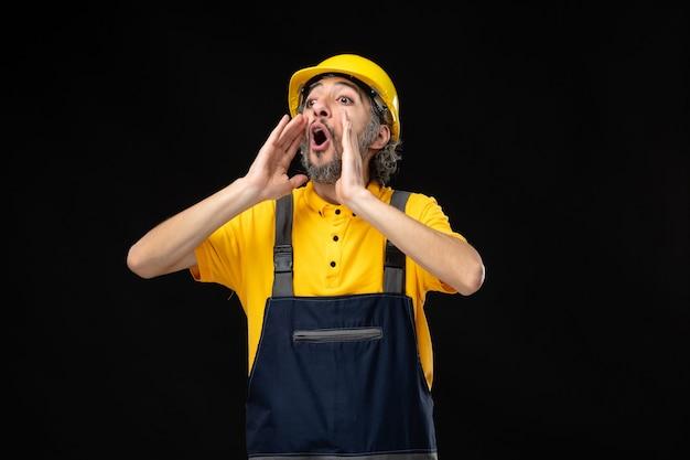 Vue de face constructeur masculin en uniforme sur mur noir