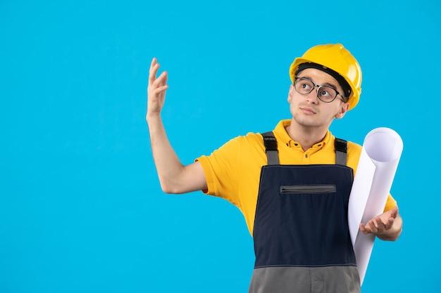 Vue de face constructeur masculin en uniforme avec plan papier sur bleu
