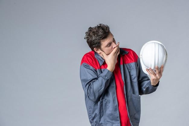 Vue de face constructeur masculin en uniforme tenant un casque sur fond clair