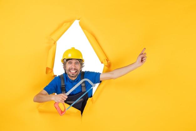 Vue de face constructeur masculin en uniforme tenant une scie à archet sur fond jaune