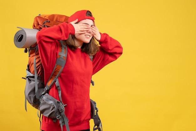 Vue de face cool femme voyageur avec sac à dos couvrant les yeux avec les mains