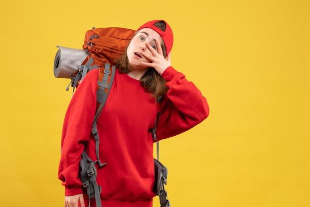 Vue de face cool femme voyageur avec sac à dos mettant la main sur son visage