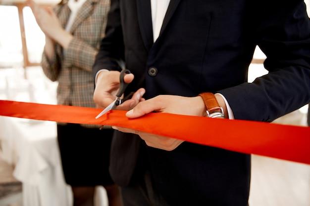 Vue de face de la coupe du ruban rouge lors de l'inauguration du bâtiment