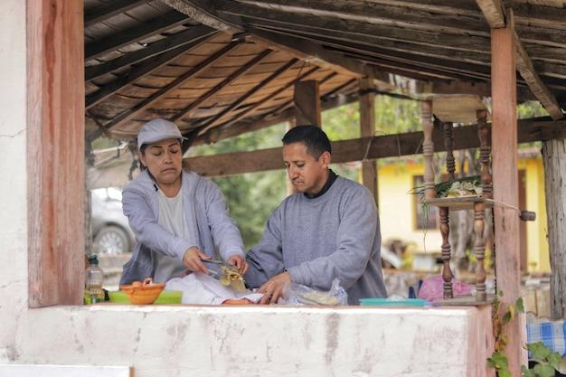 Vue de face d'un couple d'adultes de cinquante ans préparant la nourriture dans une cuisine extérieure sous un kiosque en bois dans les bois portant des vêtements de sport gris