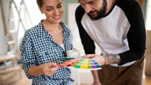 Vue de face d'un couple d'adultes moyens avec un échantillon de couleur à l'intérieur à la maison, relocalisation et concept de bricolage.