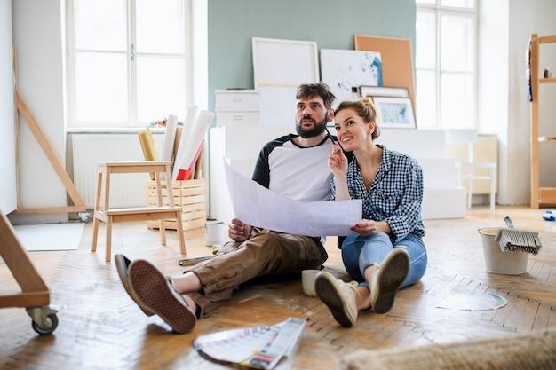 Vue de face d'un couple d'adultes moyens avec des plans de planification à l'intérieur à la maison