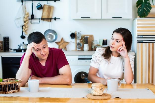 Vue de face d'un couple en colère se regardant de côté après une querelle dans la cuisine tout en prenant son petit-déjeuner à la maison. la femme est en colère contre son mari, sur le point de divorcer