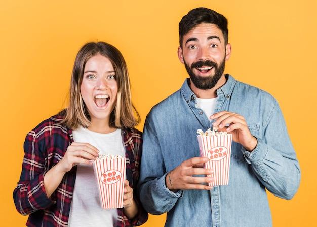 Vue de face, couple heureux avec pop-corn