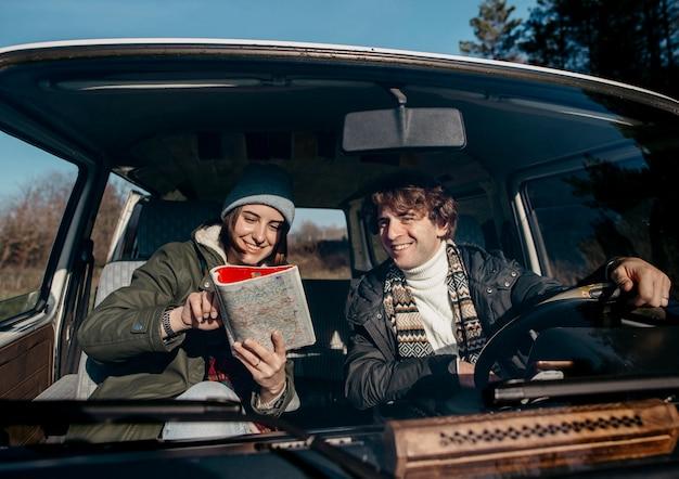 Vue de face couple regardant une carte lors d'un voyage sur la route