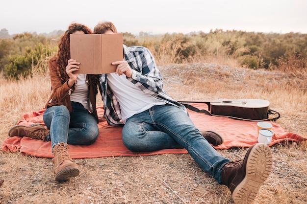 Vue de face, couple, regarder, livre