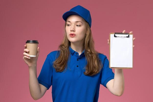 Vue de face de courrier féminin en uniforme bleu tenant une tasse de café marron avec bloc-notes sur le fond rose de l'entreprise de livraison d'uniforme d'emploi de service