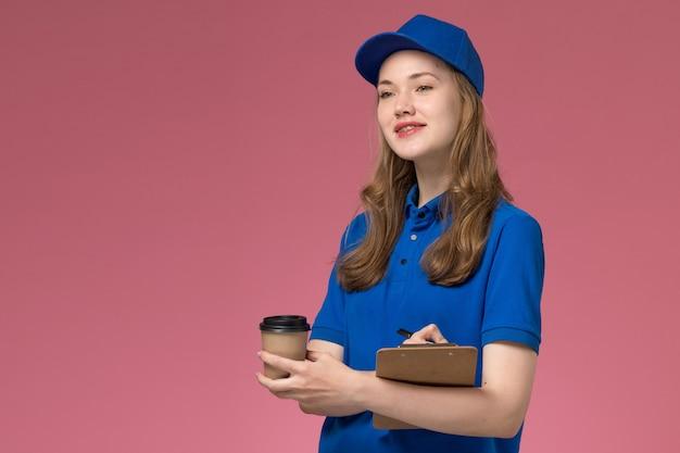Vue de face de courrier féminin en uniforme bleu tenant une tasse de café marron avec bloc-notes et sourire sur le bureau de service de bureau rose clair offrant uniforme de l'entreprise