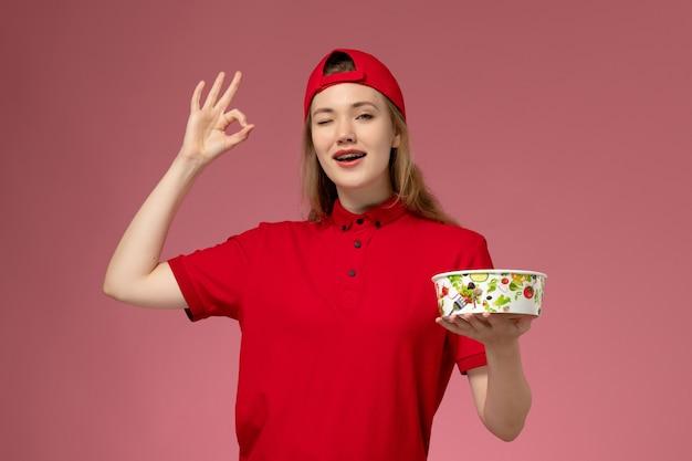 Vue de face de courrier féminin en uniforme rouge et cape tenant le bol de livraison sur le mur rose clair, la livraison d'uniforme de service