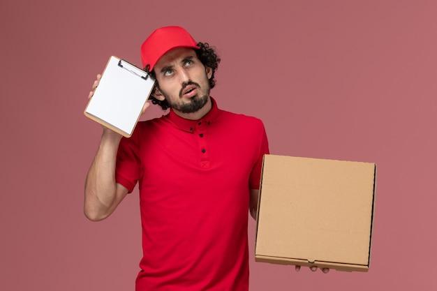 Vue de face de courrier masculin en chemise rouge et cape tenant la boîte de nourriture de livraison et le bloc-notes pensant sur le mur rose