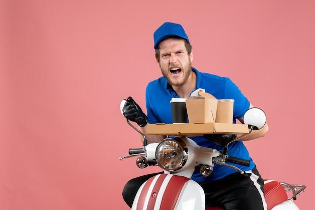 Vue de face courrier masculin en uniforme bleu tenant une boîte de café et de nourriture sur un service de couleur de vélo de travail de livraison de restauration rapide rose