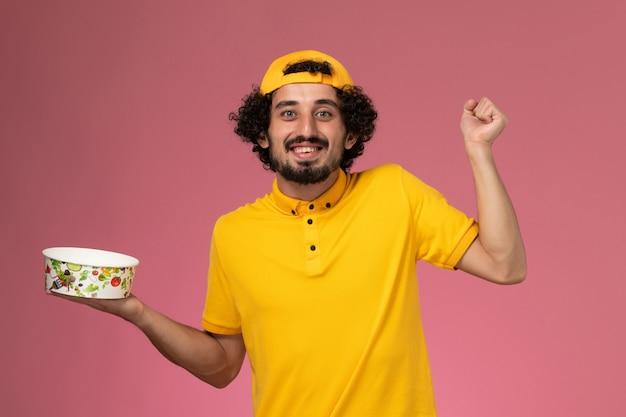 Vue de face de courrier masculin en uniforme jaune et cape avec bol de livraison rond sur ses mains se réjouissant sur le fond rose.