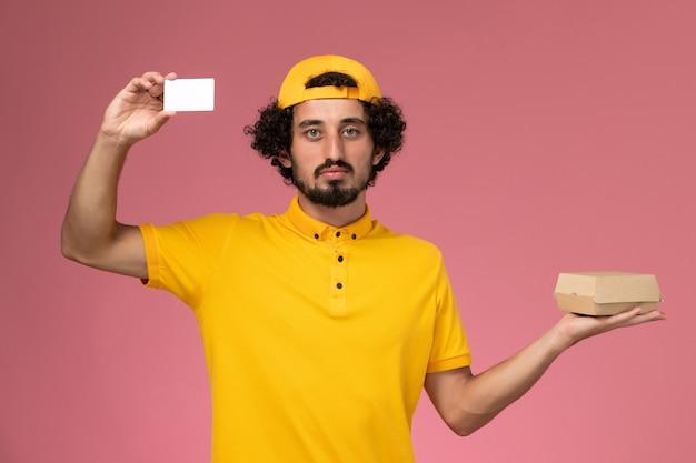 Vue de face de courrier masculin en uniforme jaune et cape avec carte et petit paquet de nourriture de livraison sur ses mains sur le fond rose clair.