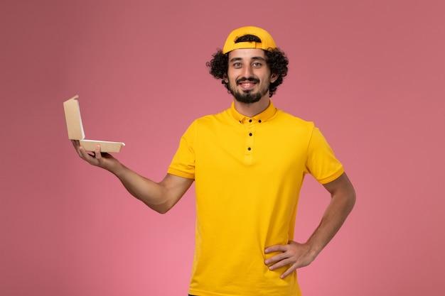 Vue de face de courrier masculin en uniforme jaune et cape avec petit paquet de nourriture de livraison ouvert sur ses mains sur fond rose.