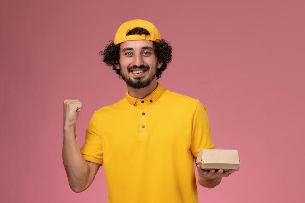 Vue de face de courrier masculin en uniforme jaune et cape avec petit paquet de nourriture de livraison sur ses mains et se réjouissant sur le fond rose.