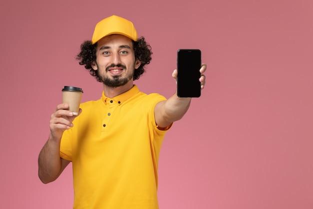 Vue de face de courrier masculin en uniforme jaune et cape tenant la tasse de café de livraison et téléphone sur mur rose