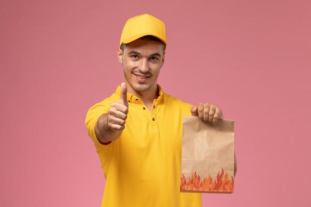 Vue de face de courrier masculin en uniforme jaune souriant et tenant le paquet de nourriture sur le fond rose