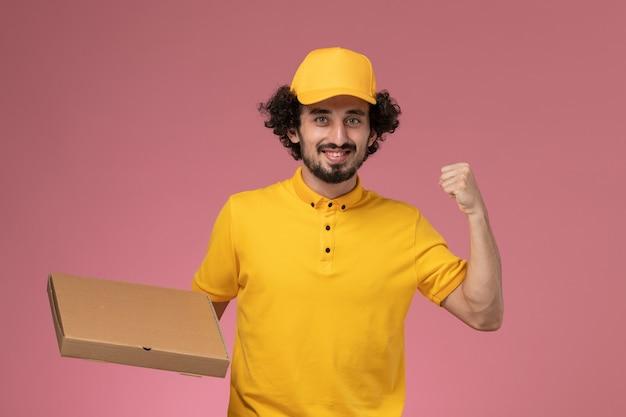 Vue de face de courrier masculin en uniforme jaune tenant la boîte de livraison de nourriture applaudissant sur le mur rose clair