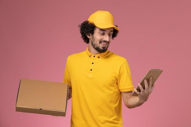 Vue de face de courrier masculin en uniforme jaune tenant la boîte de livraison de nourriture et le bloc-notes souriant sur mur rose
