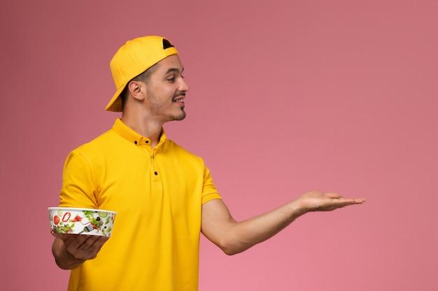 Vue de face de courrier masculin en uniforme jaune tenant des bols de livraison sur le fond rose clair.