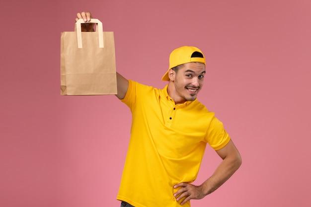 Vue de face de courrier masculin en uniforme jaune tenant le paquet de papier de livraison sur fond rose clair.
