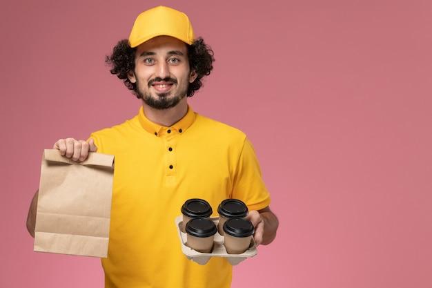 Vue de face de courrier masculin en uniforme jaune tenant des tasses de café de livraison marron et emballage alimentaire sur le mur rose