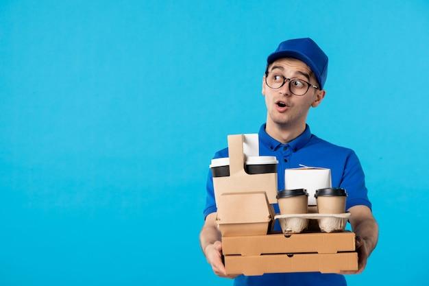 Vue de face de courrier masculin en uniforme avec livraison de nourriture et de café sur un bleu