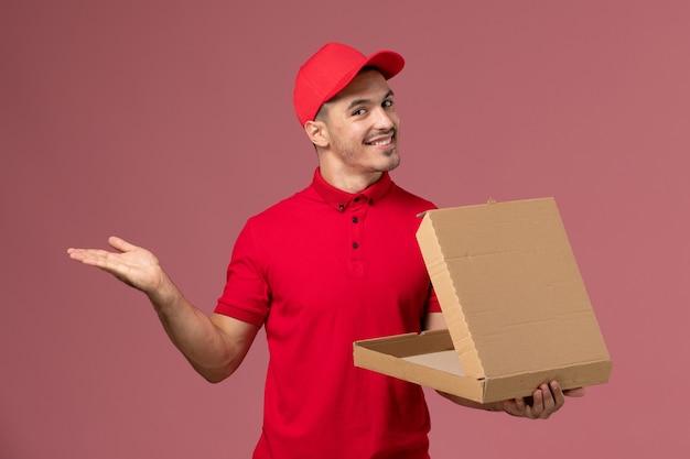 Vue de face de courrier masculin en uniforme rouge et cape tenant une boîte de nourriture avec sourire sur mur rose clair