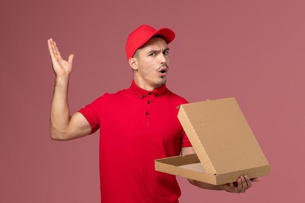 Vue de face de courrier masculin en uniforme rouge et cape tenant la boîte de nourriture avec un sourire sur le mur rose de travail de service de l'homme uniforme de livraison