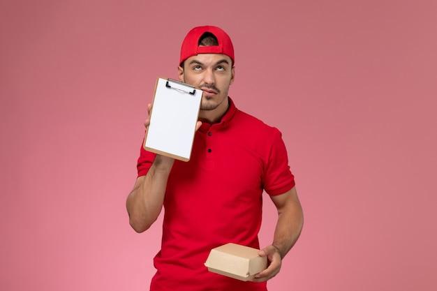 Vue de face de courrier masculin en uniforme rouge et cape tenant peu de colis de livraison avec bloc-notes sur fond rose.