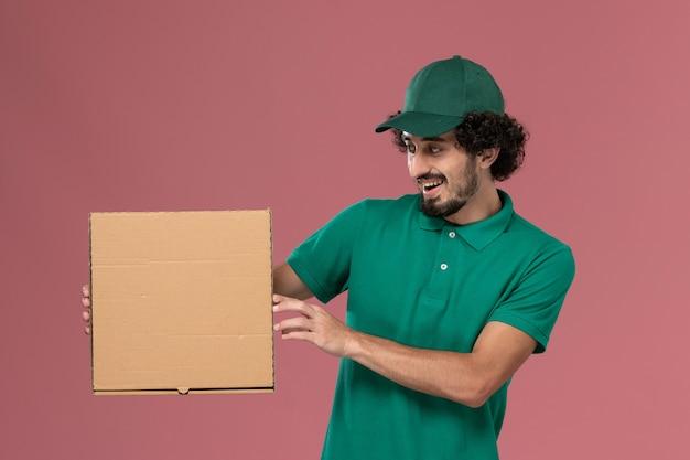 Vue de face de courrier masculin en uniforme vert et cape tenant la boîte de nourriture de livraison sur le fond rose service travail de livraison uniforme