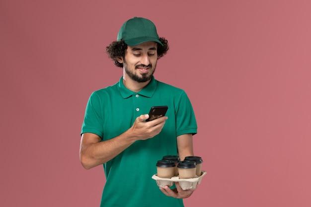 Vue de face de courrier masculin en uniforme vert et cape tenant des tasses à café en prenant une photo d'eux sur fond rose service de livraison uniforme de travail de travailleur masculin