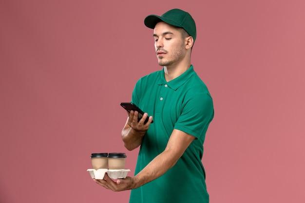 Vue de face de courrier masculin en uniforme vert prenant une photo de café sur fond rose