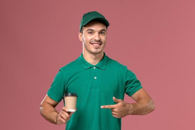 Vue de face de courrier masculin en uniforme vert souriant et tenant une tasse de café sur le fond rose