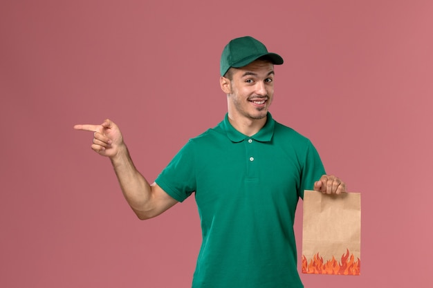 Vue de face de courrier masculin en uniforme vert tenant un paquet de papier alimentaire avec sourire sur fond rose clair