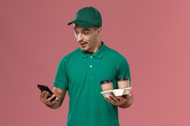 Vue de face de courrier masculin en uniforme vert tenant des tasses de café brun et à l'aide d'un téléphone avec expression surprise sur rose