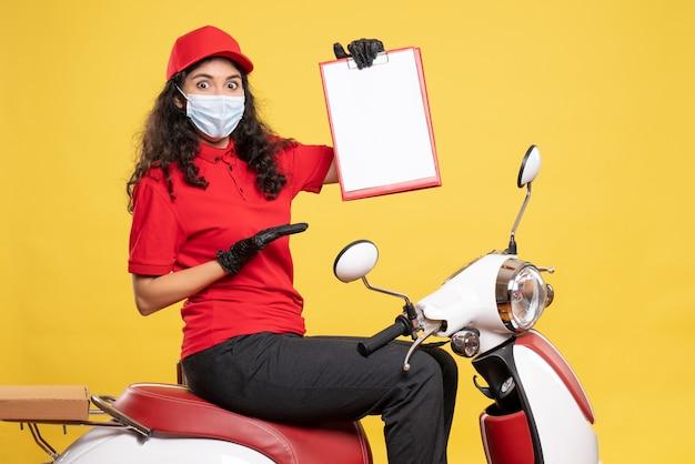 Vue de face coursier féminin dans un masque tenant une note de fichier sur fond jaune covid-livraison d'emploi uniforme travailleur service travail pandémie