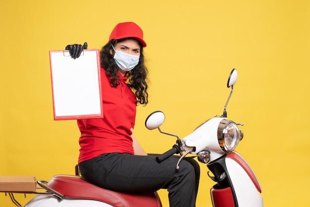 Vue de face coursier féminin dans un masque tenant une note de fichier sur fond jaune covid- travail uniforme travailleur livraison pandémie