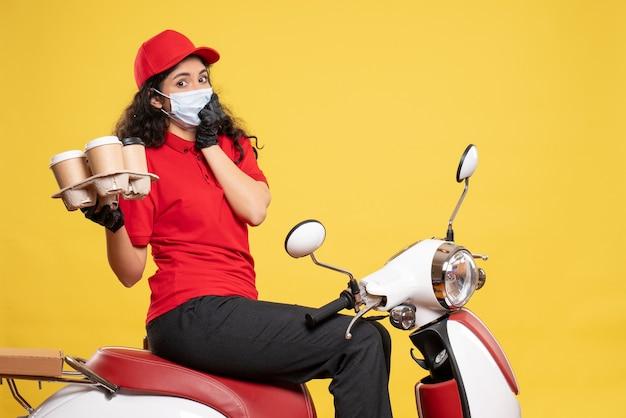 Vue de face coursier féminin en masque avec des tasses à café sur fond jaune service de livraison de travailleur pandémique covid- job