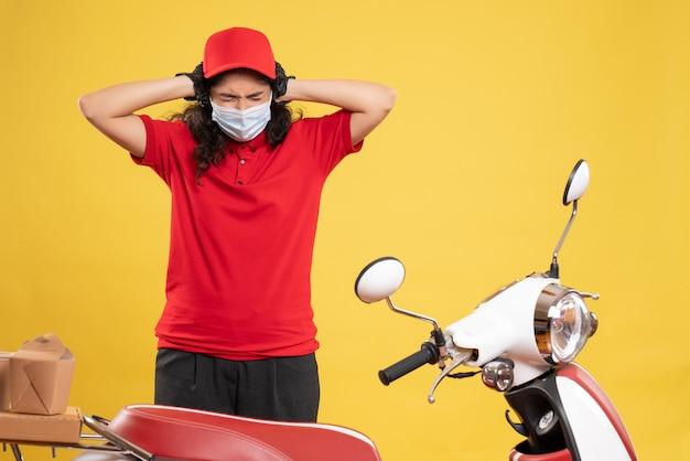 Vue de face coursier féminin en uniforme rouge et masque sur fond jaune covid - prestation de service d'emploi uniforme travailleur pandémie