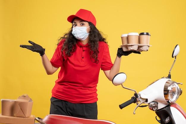 Vue de face coursier féminin en uniforme rouge avec des tasses à café sur fond jaune livraison de travailleur covid- travail de virus de service pandémique