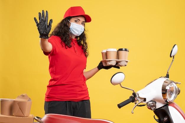 Vue de face coursier féminin en uniforme rouge avec des tasses à café sur fond jaune travailleur covid- virus de service uniforme de travail pandémique