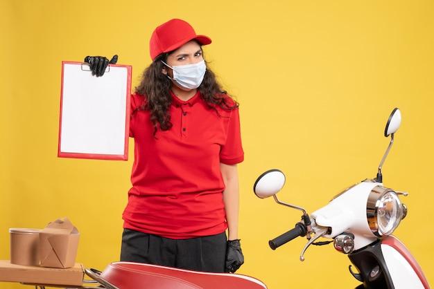Vue de face coursier féminin en uniforme rouge tenant une note de fichier sur fond jaune livraison covid-service uniforme travail de travailleur