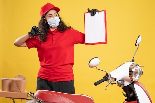 Vue de face coursier féminin en uniforme rouge tenant une note de fichier sur le fond jaune livraison covid-service uniforme travailleur pandémie emploi