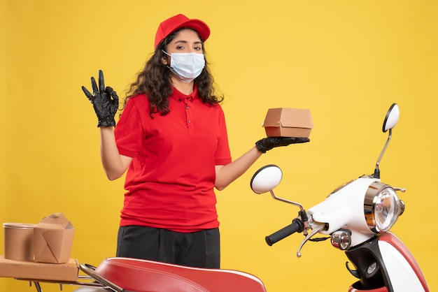 Vue de face coursier féminin en uniforme rouge tenant un petit paquet de nourriture sur fond jaune livraison covid-service uniforme travailleur pandémie
