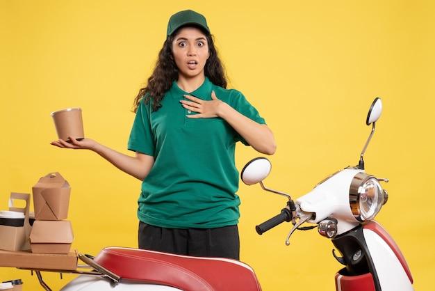Vue de face coursier féminin en uniforme vert avec dessert sur fond jaune clair travail de livraison de travail de couleur femme de service alimentaire